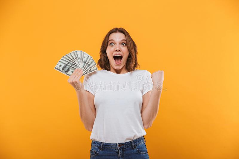 拿着金钱的情感少妇做优胜者姿态 免版税库存照片