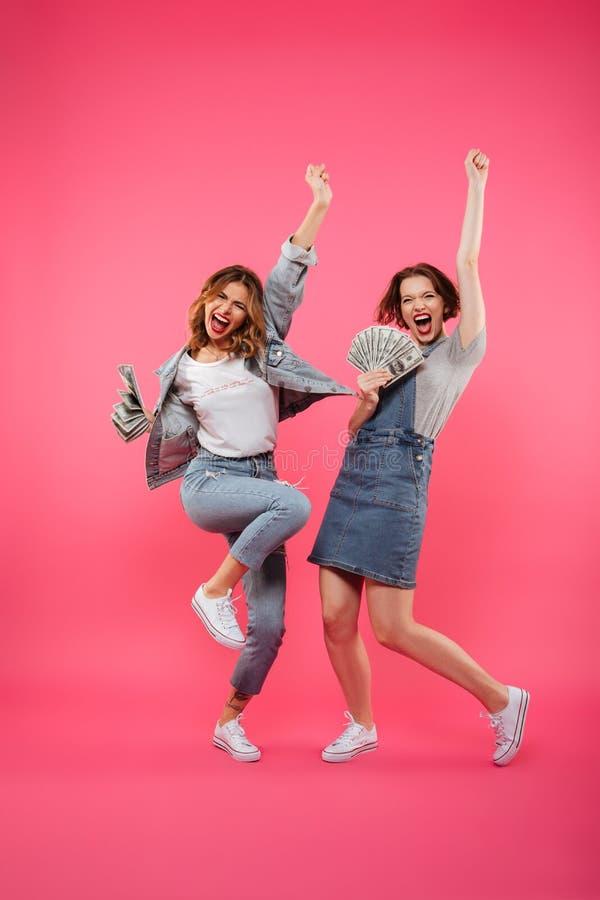 拿着金钱的情感相当两个妇女朋友 免版税图库摄影