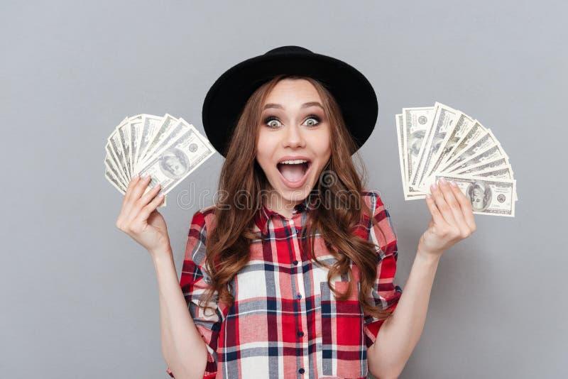 拿着金钱的愉快的年轻深色的夫人 免版税图库摄影