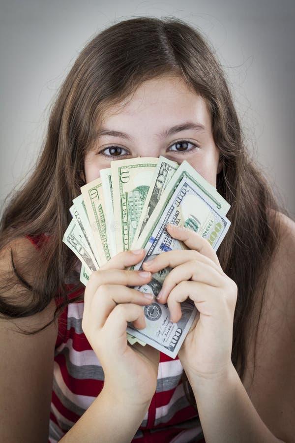 拿着金钱的美丽的青少年的女孩 图库摄影