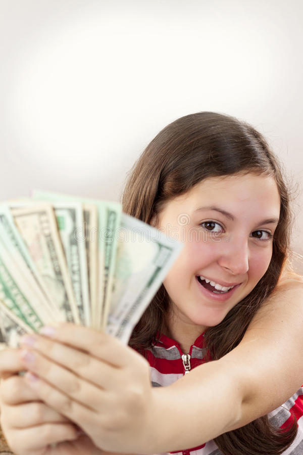 拿着金钱的美丽的青少年的女孩 库存图片
