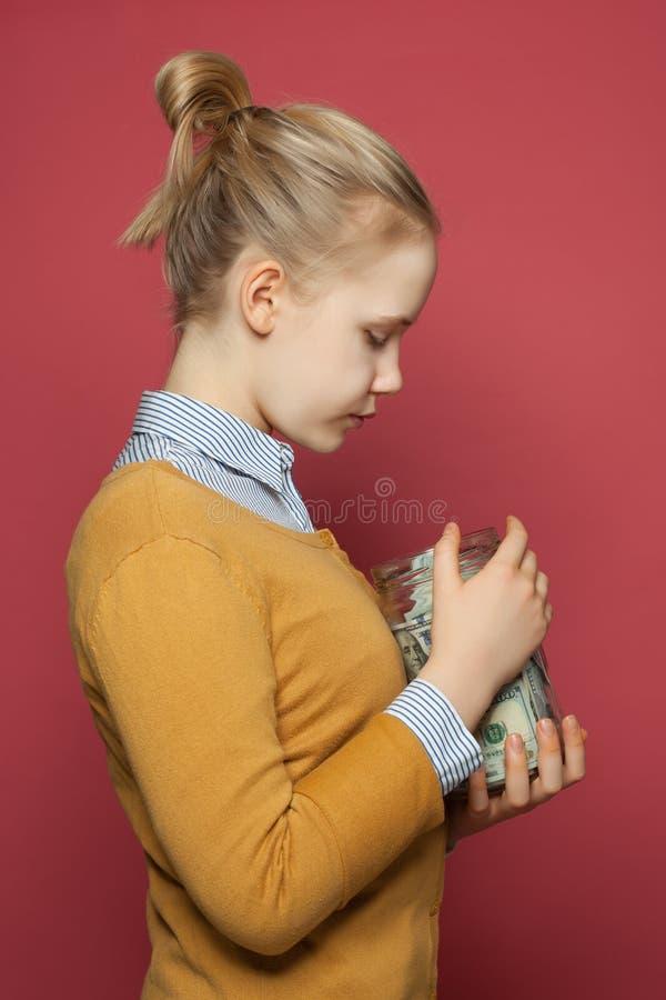 拿着金钱的逗人喜爱的少年女孩获利瓶子 学生费、责任和攒钱概念 图库摄影