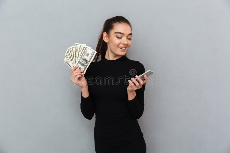 拿着金钱的黑衣裳的微笑的深色的妇女 图库摄影