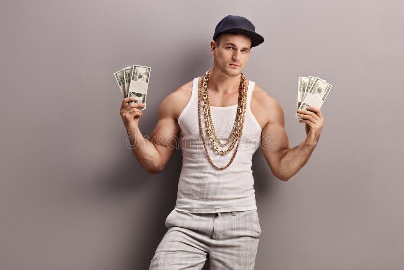 拿着金钱的年轻男性交谈者 免版税库存图片