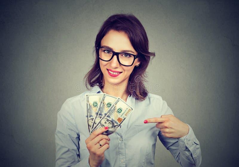 拿着金钱美金的愉快的激动的成功的女商人手中 库存图片