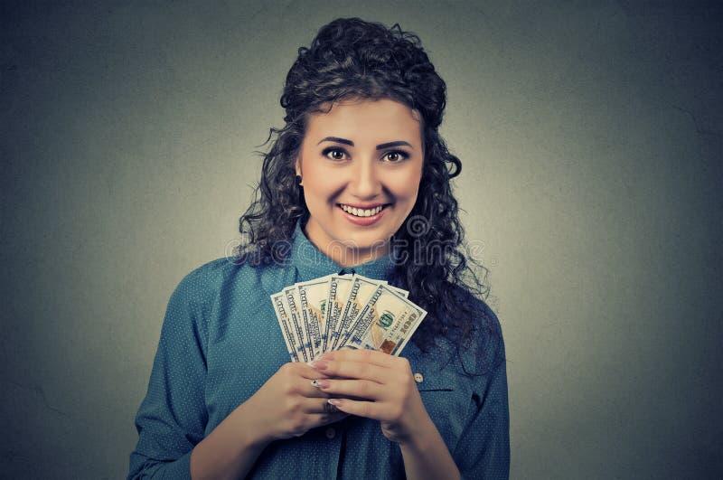 拿着金钱美金的愉快的激动的成功的年轻女商人手中 免版税图库摄影