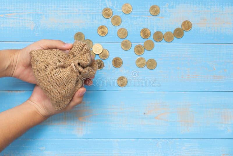 拿着金钱袋装或请求与在蓝色木背景的硬币 库存照片