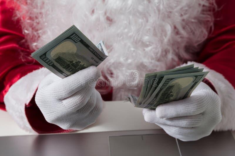 拿着金钱,美元的圣诞老人项目的手 计数纸币,付款,购物的概念 免版税库存照片