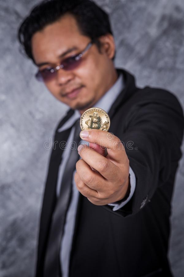 拿着金黄bitcoin的人手中 免版税库存图片