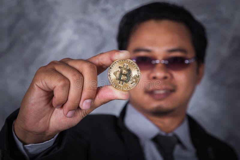 拿着金黄bitcoin的人手中 库存图片