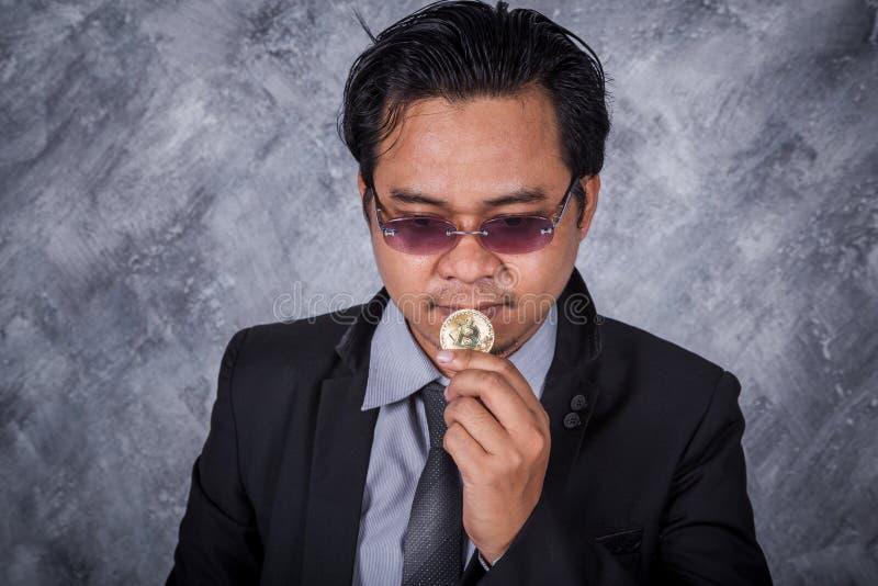 拿着金黄bitcoin的人手中 图库摄影