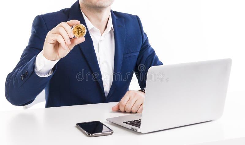 拿着金黄bitcoin的商人,当与膝上型计算机和电话一起使用在白色背景时的桌上 库存照片