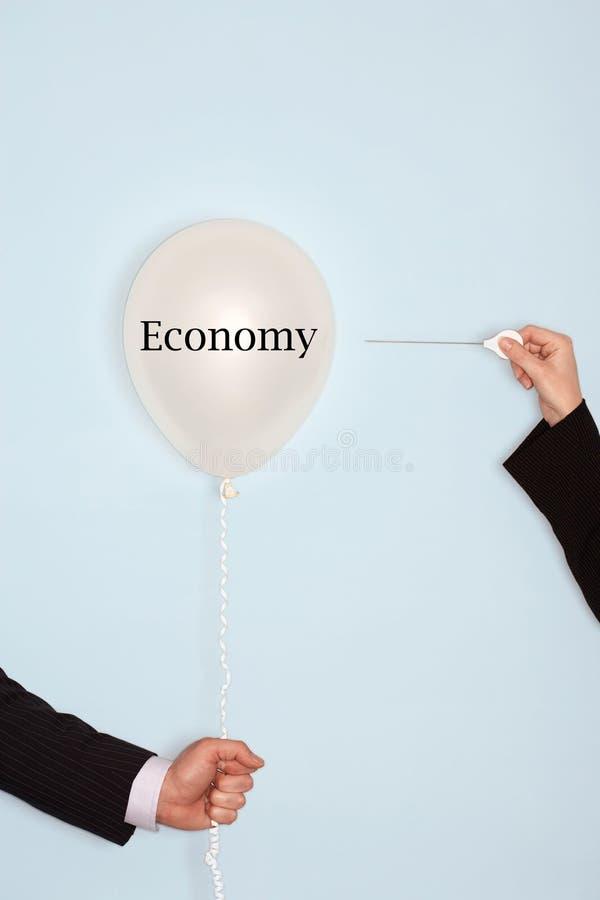拿着针和流行气球的播种的手反对与说的文本的浅兰的背景经济 免版税库存图片