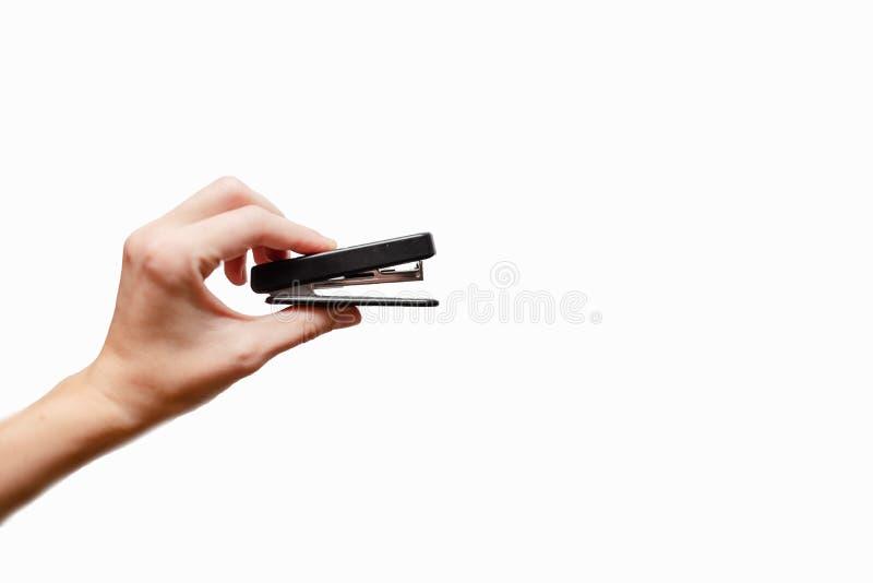 拿着钉书针的女性手 免版税库存图片