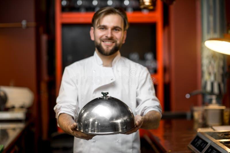 拿着钓钟形女帽的厨师厨师 库存照片