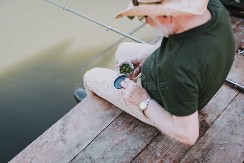 拿着钓鱼的一个年迈的人的顶视图诱饵 图库摄影