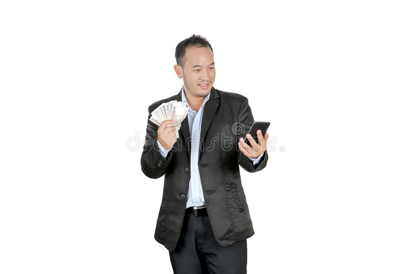 拿着钞票和看他的手机的愉快的亚洲商人 免版税图库摄影