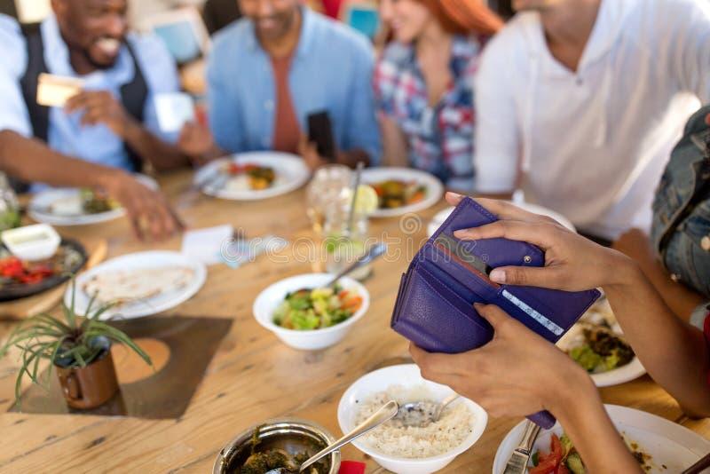 拿着钱包的女性手在餐馆 免版税库存图片