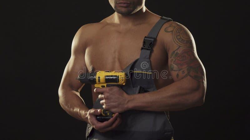 拿着钻子的一位musuclar性感的赤裸上身的被剥去的安装工的播种的射击 免版税库存照片