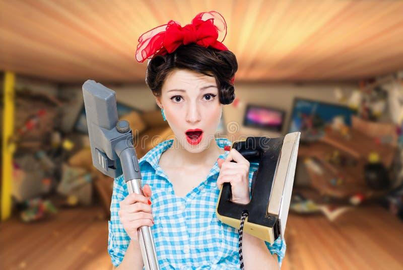 拿着铁和真空吸尘器的年轻可爱的妇女 免版税库存图片