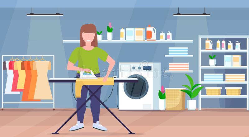 拿着铁微笑的女孩的主妇电烙的衣裳年轻女人做家事概念现代洗衣房内部 向量例证