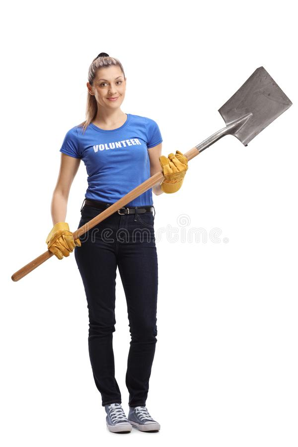拿着铁锹的年轻女性志愿者 免版税库存照片