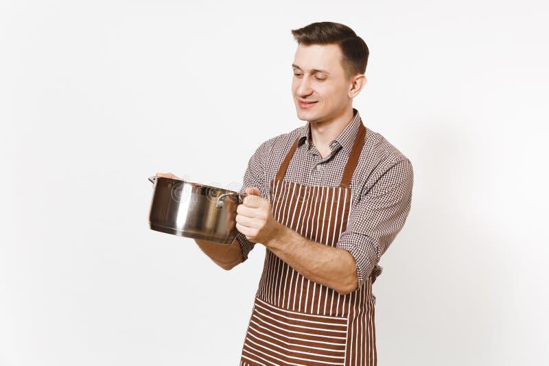 拿着银色不锈的光滑的铝空stewpan,平底锅或者罐的镶边棕色围裙的人厨师隔绝在白色 免版税库存图片