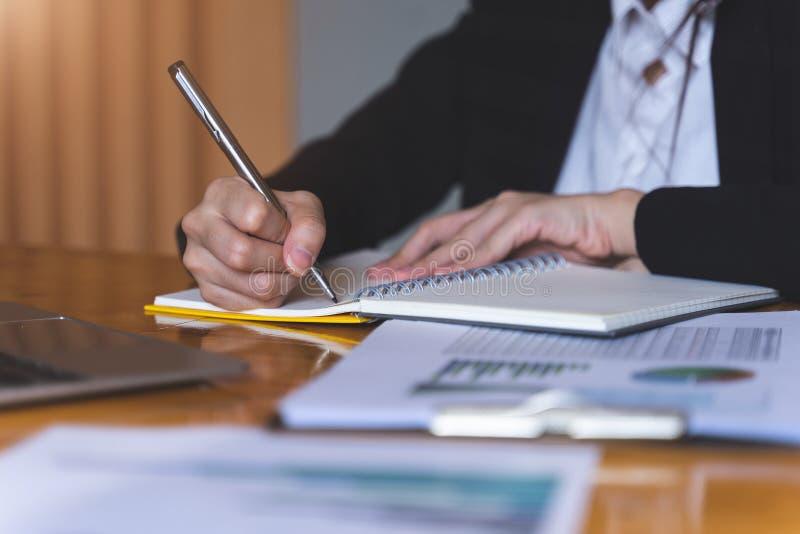 拿着银色笔的女实业家或秘书准备好做在被打开的笔记本板料的笔记 企业财务和秘书概念 库存照片
