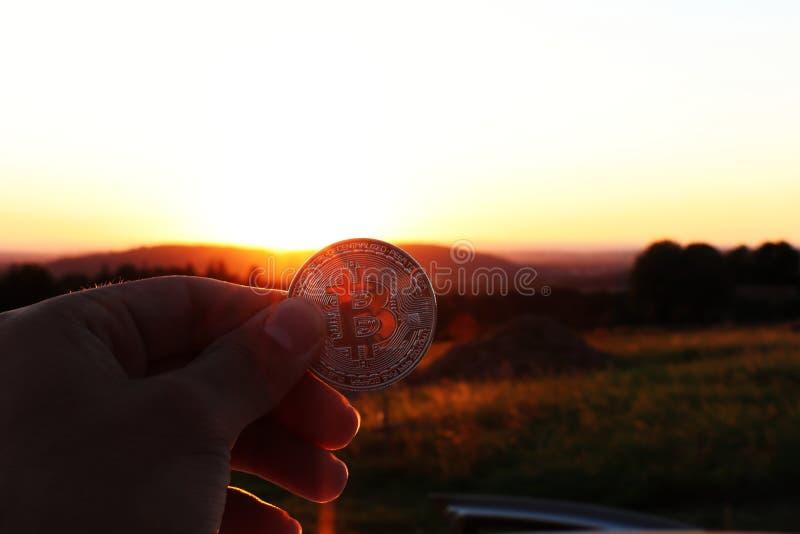 拿着银色bitcoin在那里背景中的投资者是令人敬畏的日落 免版税库存照片