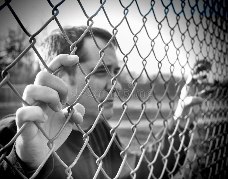拿着链篱芭障碍的生气人 库存照片
