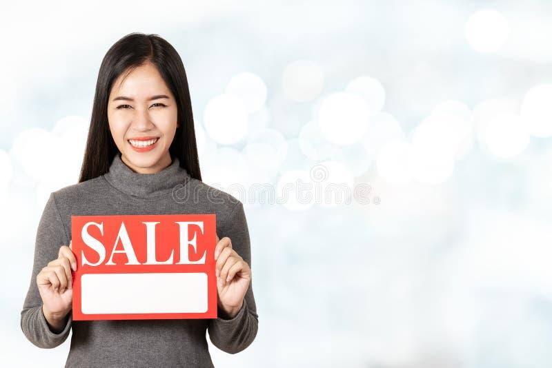 拿着销售牌卡片的年轻可爱的亚裔妇女显示为看照相机的价牌 免版税库存图片