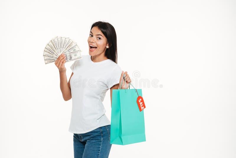 拿着销售购物袋的一名激动的愉快的妇女的画象 免版税库存图片