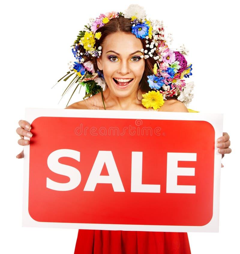 拿着销售额横幅和花的妇女。 免版税库存图片