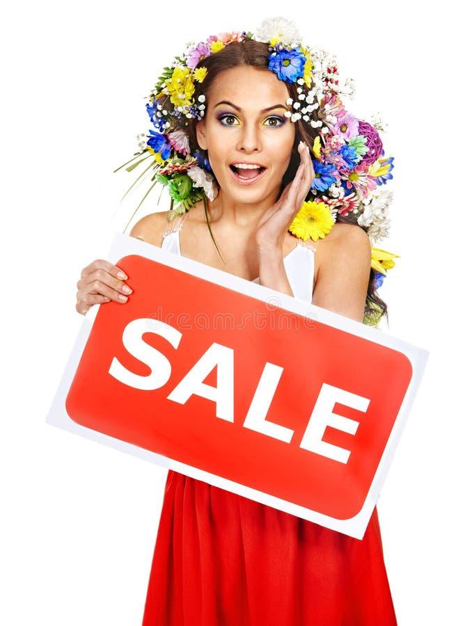 拿着销售额横幅和花的妇女。 库存照片