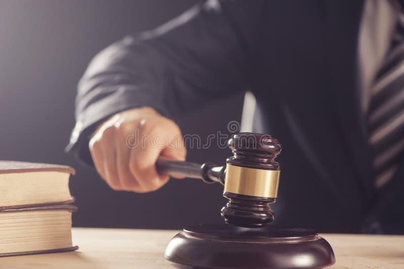 拿着锤子或惊堂木的法官的手. 陪审员, 规章制度.