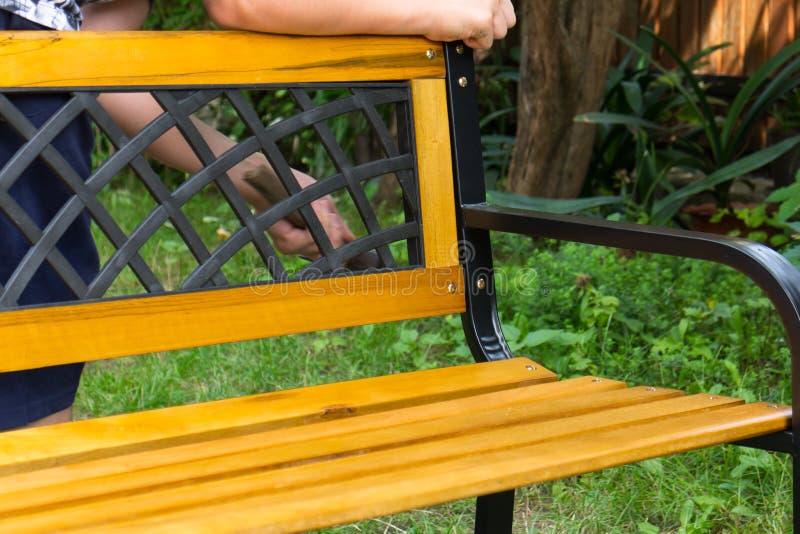 拿着锤子的一个人,当修理长凳时 免版税图库摄影
