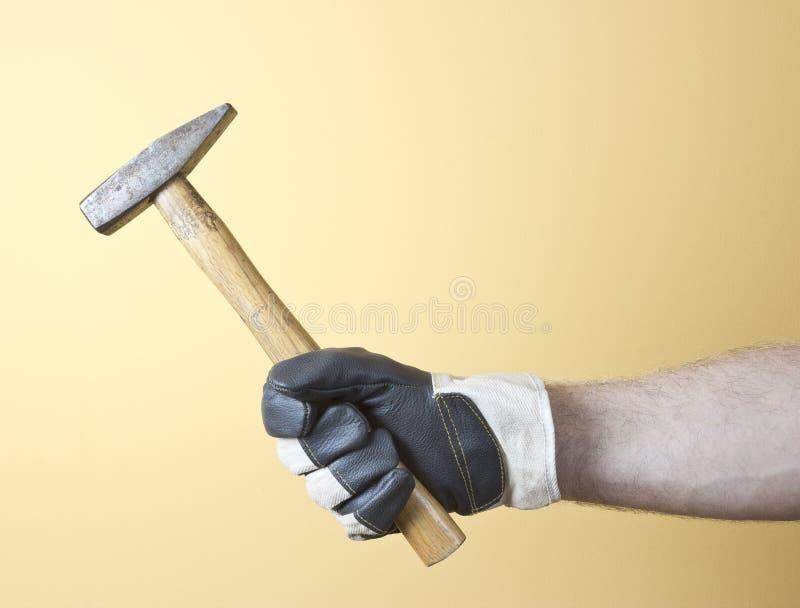 在拿着锤子的工作者手套的手