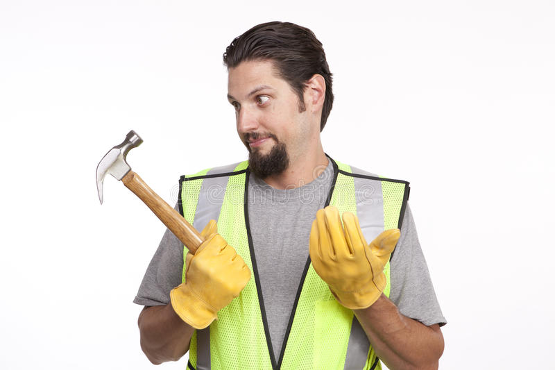 拿着锤子的迷茫的建筑工人 库存照片