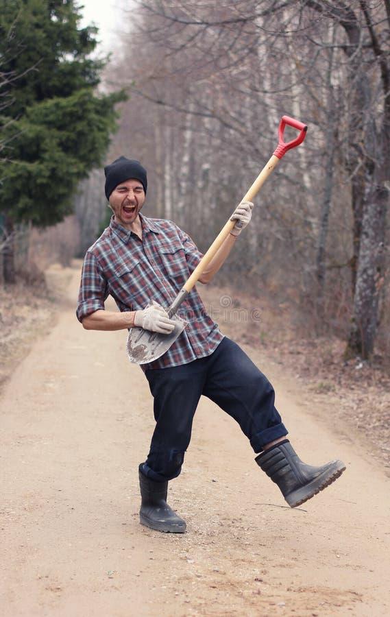 拿着锹的花匠或农夫人喜欢吉他 工作在t 免版税库存照片
