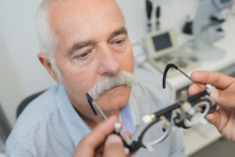 拿着镜片为的眼科医生试验 免版税库存图片