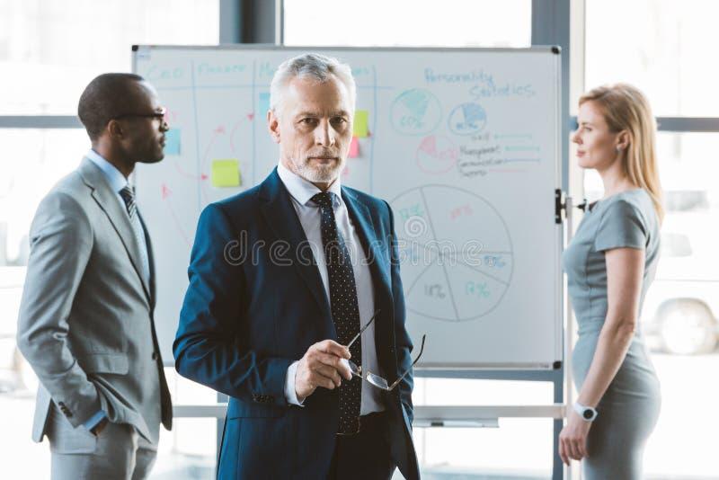 拿着镜片和看照相机的确信的资深商人,当企业同事身分时 库存图片