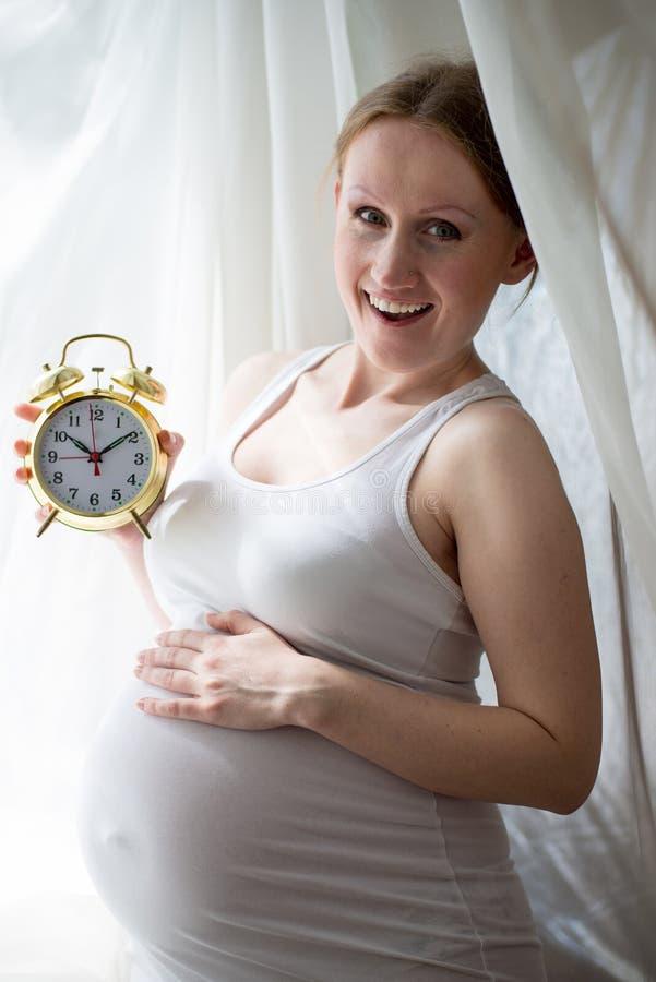 拿着闹钟怀孕的美丽的小姐 免版税库存图片