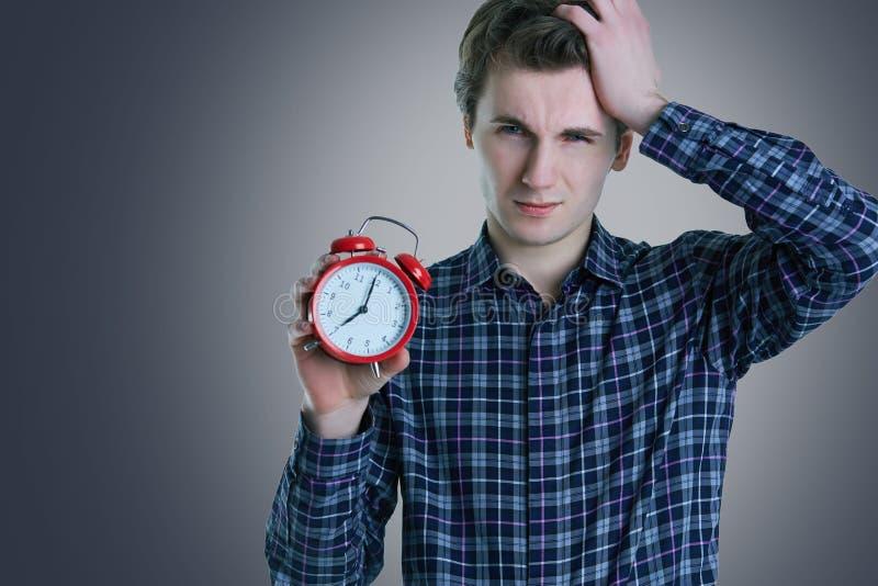 拿着闹钟的一个混乱的年轻人的特写镜头画象被隔绝在白色背景 免版税库存图片