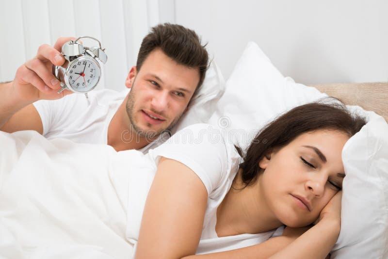 拿着闹钟的人醒来她的妻子 免版税图库摄影