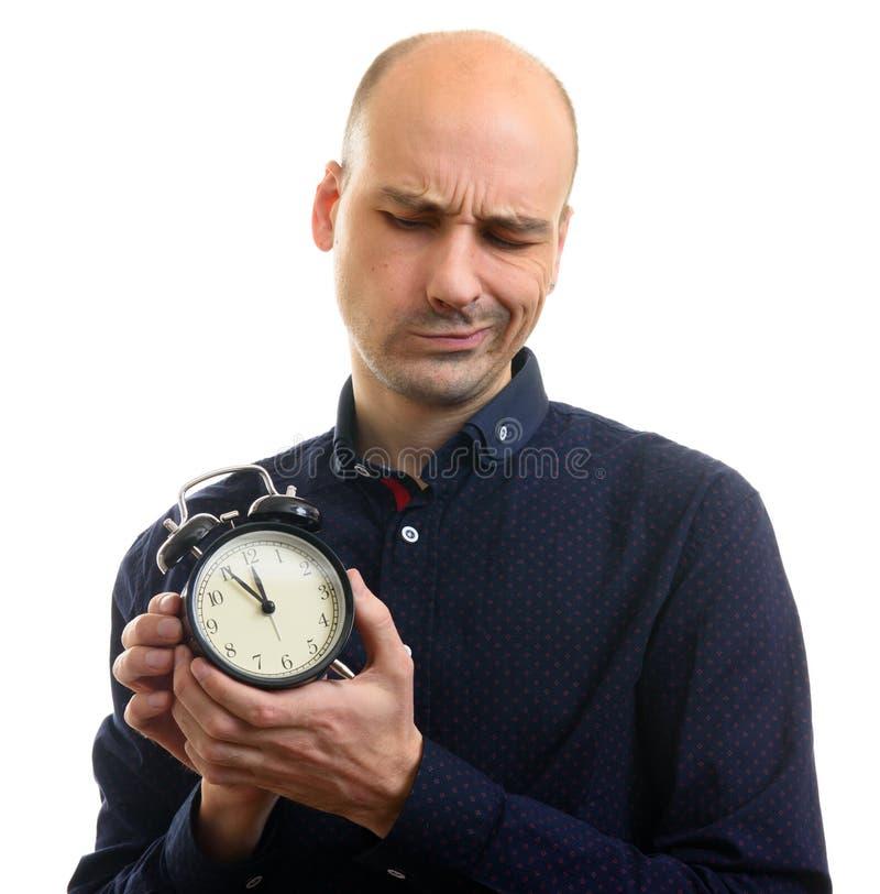 拿着闹钟的怀疑秃头人 库存照片