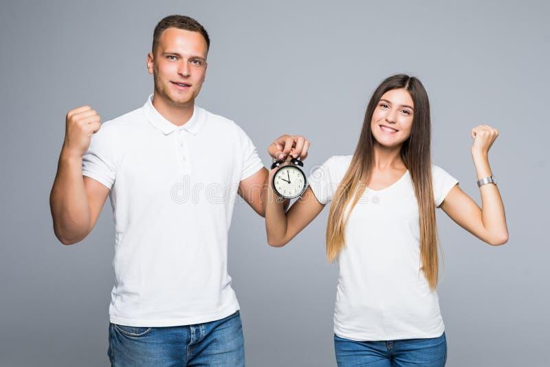 拿着闹钟的愉快的年轻爱恋的夫妇画象在灰色背景做优胜者姿态被隔绝 免版税库存图片