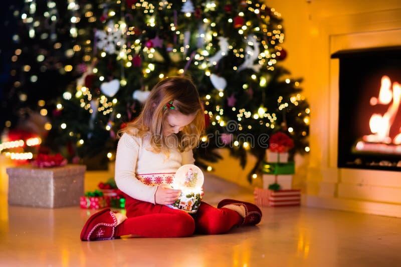 拿着雪地球的小女孩在圣诞树下 免版税库存照片