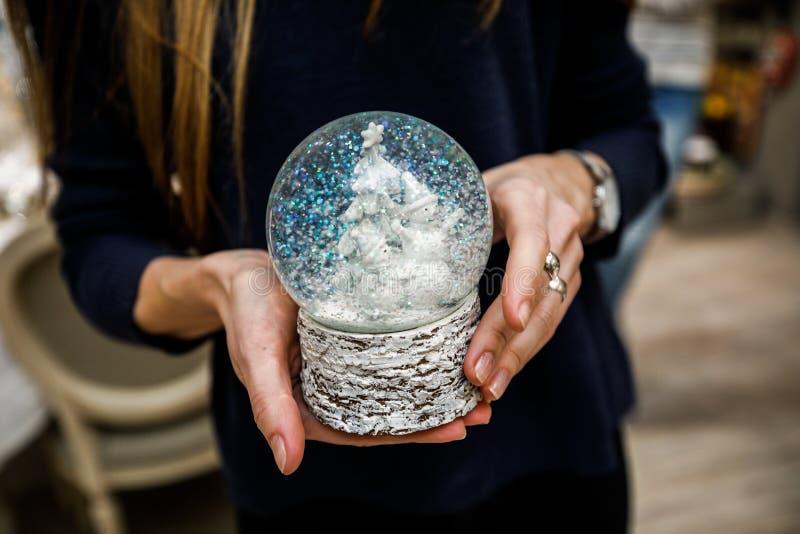 拿着雪地球的被编织的套头衫的女孩 免版税库存图片