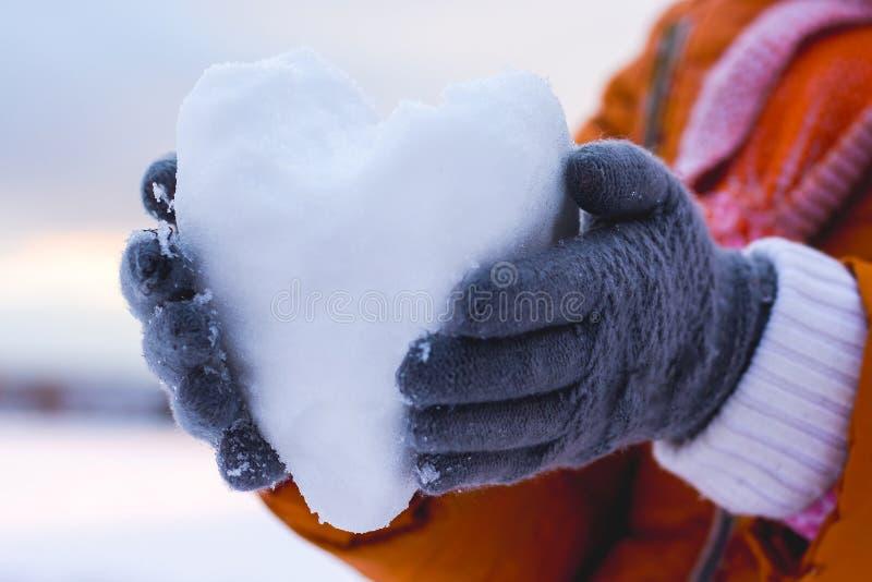 拿着雪的心脏女孩,愿望祝贺她的朋友 免版税图库摄影