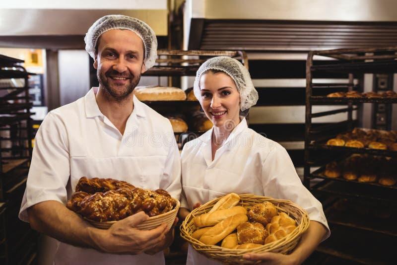 拿着面包和甜食物的篮子女性和男性面包师画象  免版税库存图片